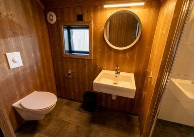 Bad med toalett, vindu, vask og speil