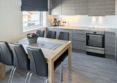 Kjøkken med spisebord, stoler og ovn