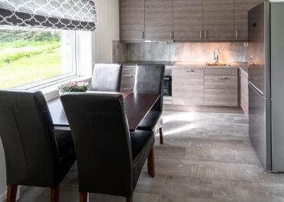 Kjøkken med spisebord, stoler, kjøleskap, vask og ovn