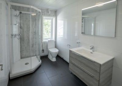 Bad med toalett, dusj, vask, speil og vindu